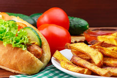 Fast food meal, hot dog, french fries, ketchup, tomato and cucumber on wooden background. Stock Photos