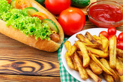Fast food meal, hot dog, french fries, ketchup, tomato and cucumber on wooden background. Royalty Free Stock Image