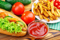 Fast food meal, hot dog, french fries, ketchup, tomato and cucumber on wooden background. Royalty Free Stock Images
