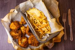 Fast food meal served on the table. Meat and french fries in the food boxes. Unhealthy food in the paper boxes. Chicken meat with royalty free stock photos