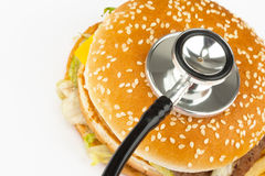 Fast food with medical stethoscope stock images