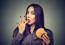 Fast food is my favorite. Woman eating a hamburger enjoying the taste Stock Photo