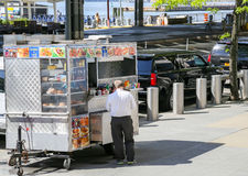 Fast Food in NY. New York City, USA - May 19, 2014: A fast food stand at the seaport in lower manhattan. A salesman waits for costumers Royalty Free Stock Photo