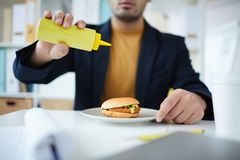 Fast food. Office manager adding mustard from plastic bottle to his hamburger before eating it Stock Photo