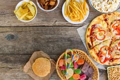 Fast food on old wooden background. Concept of junk eating. Top view stock photos