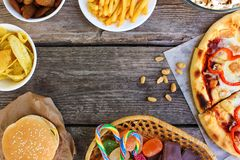 Fast food on old wooden background. Concept of junk eating. Top view stock image