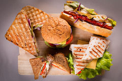 Fast food plate with burger hot dog sandwiches chicken wrap. Fast food plate with burger hot dog sandwiches and chicken wrap Stock Photos