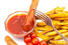 Fast food, portion of french fries, ketchup, cherry tomato, grilled sausages on fork isolated on white background. Stock Photo