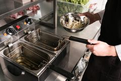 Fast food preparing french fries unhealthy eating. French fries - best junk food ever. Cook preparing fast food in the restaurant kitchen. Unhealthy and Stock Photo