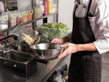 Fast food preparing french fries unhealthy eating. French fries - best junk food ever. Cook preparing fast food in the restaurant kitchen. Unhealthy and Stock Image