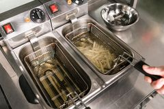 Fast food preparing french fries unhealthy eating. French fries - best junk food ever. Cook preparing fast food in the restaurant kitchen. Unhealthy and Royalty Free Stock Photos
