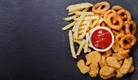 Fast food products: onion rings, french fries and chicken nuggets. On dark table, top view stock photography