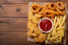 Fast food products: onion rings, french fries and chicken nuggets. On wooden table, top view royalty free stock images