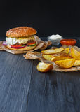 Fast food restaurant dish. Hamburger and fries wedges Royalty Free Stock Photography