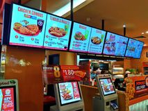 Fast food restaurant. Modern self-service food ordering kiosks and menus in Popeyes, a fast food restaurant in Singapore royalty free stock photo