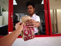 A fast food restaurant worker hands over an order of food to a customer at a drive thru counter. Stock Images