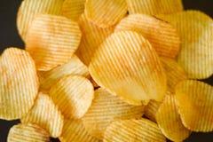 Fast food ridged chips recipe fried potato slices. Fast food. waved ridged chips recipe. golden fried spicy potato slices mix background stock photos