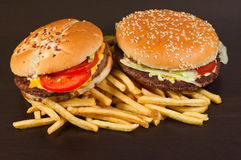 Fast food set big hamburger and french fries. On black background Stock Photos