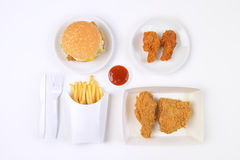 Fast food set containing burgers, fried chicken and french fries isolated on white background Royalty Free Stock Photo