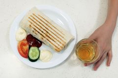 Fast food. Shaurma or doner on a white plate, next to a piece of cucumber and tomato with mayonnaise and ketchup. The boy`s hand stock image