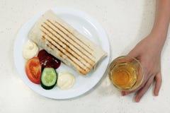 Fast food Shaurma lub doner na białym talerzu obok kawałka ogórek i pomidor z, majonezem i ketchupem Chłopiec ` s ręka obraz stock