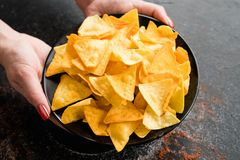 Fast food snack bad eating habit woman hands chips. Unhealthy fast food snacks. bad eating habits. woman hands holding crispy delicious nacho chips on a plate royalty free stock photography