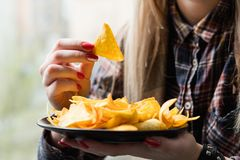 Fast food snack bad habit woman eat chips. Unhealthy fast food snacks. bad nutrition habits. woman eating crispy delicious nacho chips royalty free stock photos
