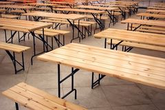 Fast food tables. Interior of an empty fast food cafe with floor of stone, wooden tables and benches Royalty Free Stock Photography