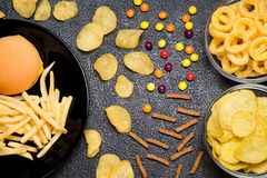 Fast food: top view of burger, french fries, chips, rings and ca. Ndies on dark background. Unhealthy eating concept Stock Photos