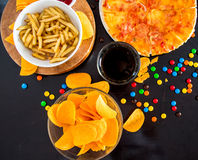 Fast food and unhealthy eating concept - close up of pizza,, french fries and potato chips and candies on wooden table top view stock photos