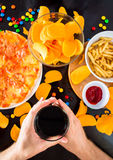 Fast food and unhealthy eating concept - close up of pizza,, french fries and potato chips and candies on wooden table top view royalty free stock image