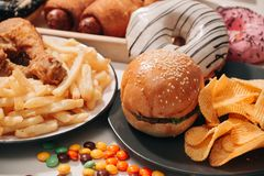 Fast food and unhealthy eating concept - close up of fast food snacks and cola drink on white table royalty free stock image