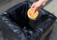 Fast food and unhealthy eating concept - hand throwing a burger in  trash on street Stock Images