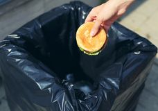 Fast food and unhealthy eating concept - hand throwing a burger in the trash Royalty Free Stock Image
