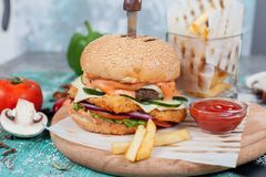 Fast food, wy?mienicie hamburger, pi?knie rozk?adaj?cy na drewnianym tle obrazy stock