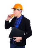 Fast food. Young man in a helmet eating burger isolated on a white background Royalty Free Stock Photo