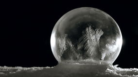 Ice globe freezing slow and brake up. Fast Freezing Soap bubble and breaking up. Frozen Ice globe on black background in cold winter. For Christmas and New Year stock video
