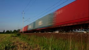 Cargo transport train loop. A fast freight train rushes around the railroad bend – loop footage. Wagons in endless and loopable motion. Cargo transport on stock video footage