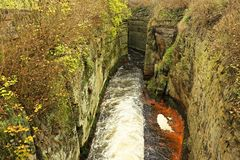 Fast full-flowing foamy water between sandstone rocks, orange sediments on dirty bank. Deep riverbed hewed into block Stock Images