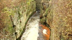 Fast full-flowing foamy water between sandstone rocks, orange sediments on dirty bank. Deep riverbed hewed into rock stock video footage