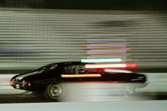 Fast car racing. Side view of black car racing with abstract light effect royalty free stock image