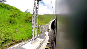 Fast-going passenger train enters the tunnel and exits it stock video footage