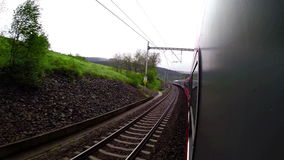A fast-going passenger train moves along the rail towards its terminal station. 