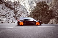 Fast hatchback car fasting through mountains. Fast sport hatchback car fasting through mountain pass Stock Photos