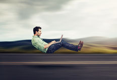 Fast internet concept. Autonomous self driving vehicle car technology. Levitating business man on road using laptop Royalty Free Stock Images
