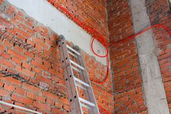 Fast ladder at the brick wall and wires stock photo