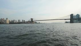 Fast low angle time lapse view on calm ocean water moving in small waves with Brooklyn bridge in background New York stock video footage