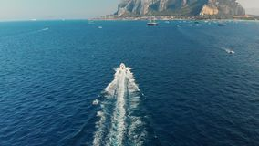 Fast luxury yacht rushes through the waves leaving a trail of foam on the turquoise ocean water. Ahead of the rocky. Mountains. The concept of overcoming stock video footage