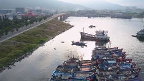 Fast motion above small bay crowded with fishing boat rows. Along highway against foggy mountains in morning aerial stock footage