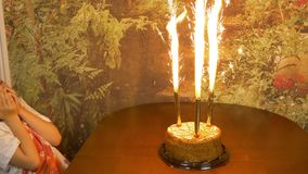 Fast motion. Girl clapping by hands. Sitting girl afraid of fire. Sparkling fire fountains in a cake. Girls Birthday. Girl clapping by hands. Sitting girl afraid stock video